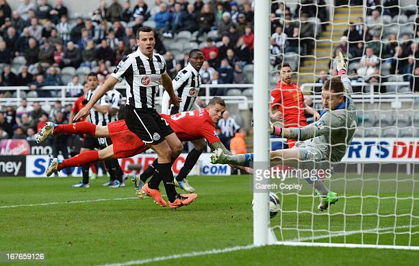Daniel Agger of Liverpool watches a free kick by Jordan Henderson of Liverpool go past goalkeeper Rob Elliot of Newcastle United for Liverpool's...