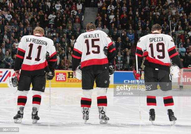 Daniel Alfredsson Dany Heatley and Jason Spezza of the Ottawa Senators line up during the National Anthem before the NHL game against the Vancouver...