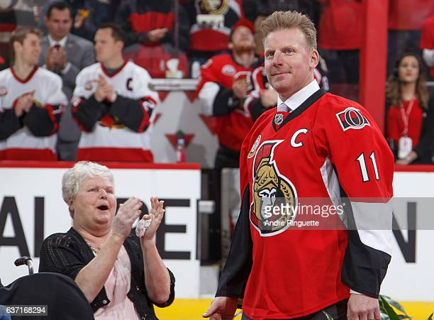 Daniel Alfredsson is introduced during his jersey retirement ceremony as his mother claps in the background prior to a game between the Ottawa...