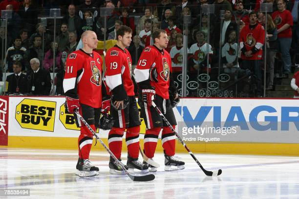 Daniel Alfredsson Jason Spezza and Dany Heatley of the Ottawa Senators stand together on the blue line during the singing of the national anthems...