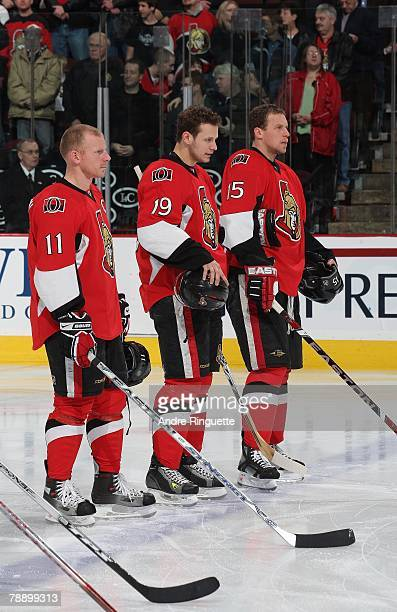 Daniel Alfredsson, Jason Spezza and Dany Heatley of the Ottawa Senators stand on the blue line as part of the starting line-up during the playing of...