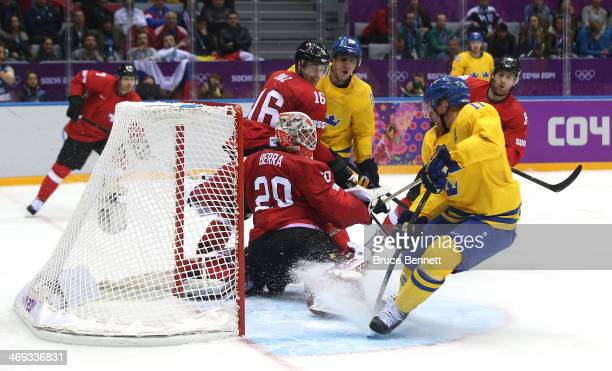 Daniel Alfredsson of Sweden shoots and scores against Reto Berra of Switzerland in the third period during the Men's Ice Hockey Preliminary Round...