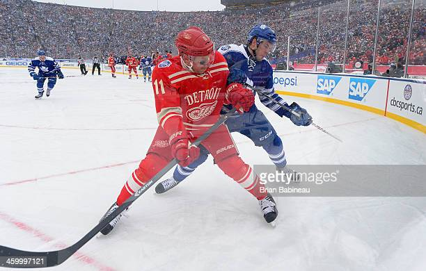 Daniel Alfredsson of the Detroit Red Wings and Peter Holland of the Toronto Maple Leafs vie for position in the corner in the second period during...