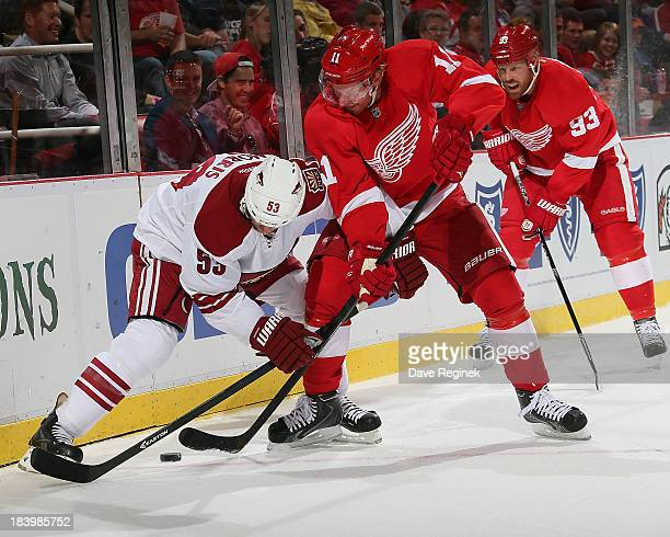 Daniel Alfredsson of the Detroit Red Wings battles for the puck with Derek Morris of the Phoenix Coyotes during an NHL game at Joe Louis Arena on...