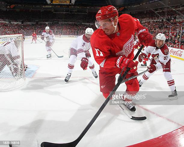 Daniel Alfredsson of the Detroit Red Wings skates with the puck in front of Derek Morris and Keith Yandle of the Phoenix Coyotes during a NHL game at...