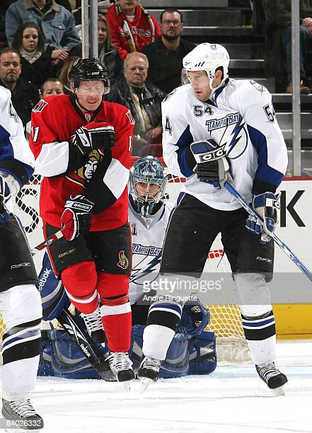 Daniel Alfredsson of the Ottawa Senators and Paul Ranger of the Tampa Bay Lightning protect themselves against a shot from the point as Mike Smith of...