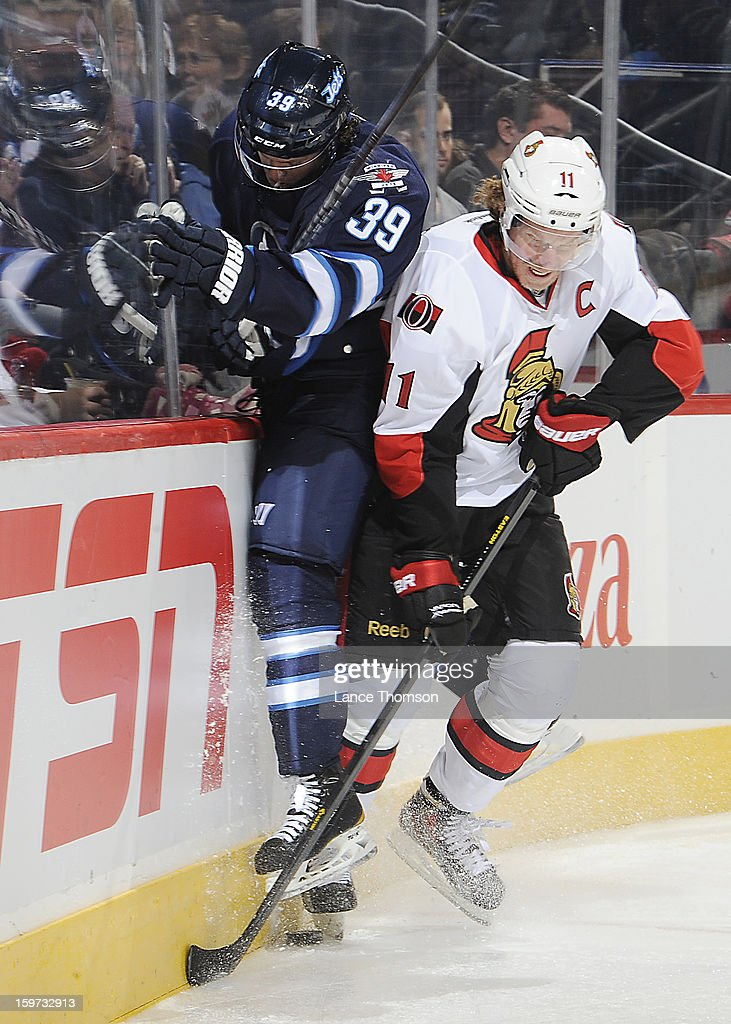 Daniel Alfredsson #11 of the Ottawa Senators checks defenseman Tobias Enstrom #39 of the Winnipeg Jets into the boards as they battle for the puck during third period action at the MTS Centre on January 19, 2013 in Winnipeg, Manitoba, Canada.