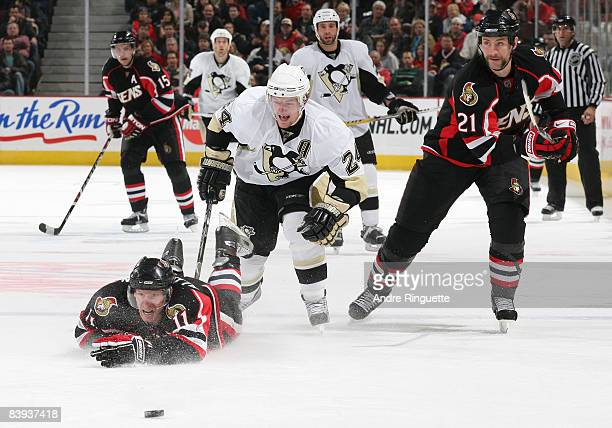 Daniel Alfredsson of the Ottawa Senators dives to glove the puck away from Matt Cooke of the Pittsburgh Penguins at Scotiabank Place on December 6,...