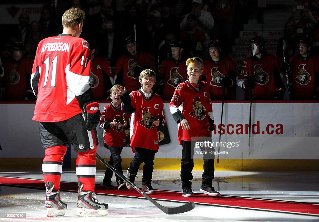 Daniel Alfredsson #11 of the Ottawa Senators greets is sons at center ice during his retirement ceremony prior to a game against the New York Islanders at Canadian Tire Centre on December 4, 2014 in Ottawa, Ontario, Canada.