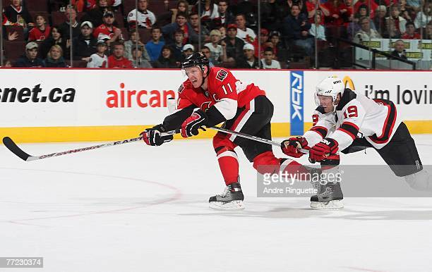 Daniel Alfredsson of the Ottawa Senators of fights off Travis Zajac the New Jersey Devils to score an empty net goal at Scotiabank Place on October...