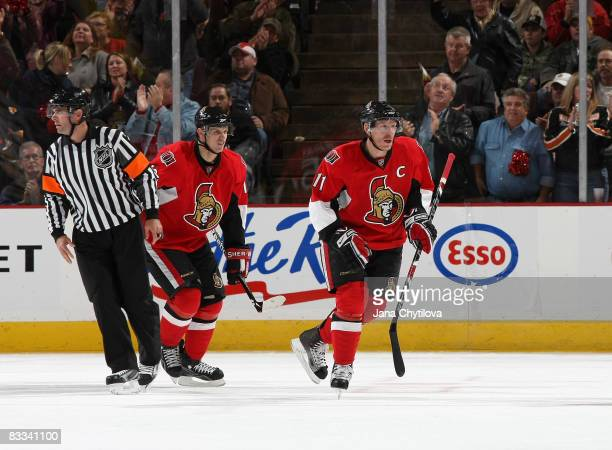 Daniel Alfredsson of the Ottawa Senators skates to the bench after scoring his first goal of the season followed by Jason Spezza of the Ottawa...