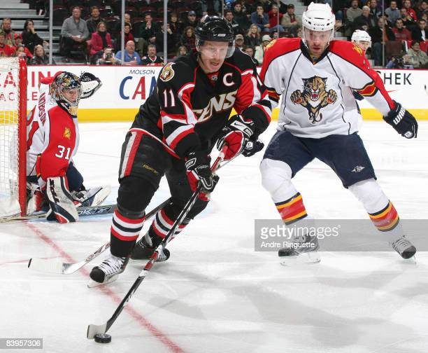 Daniel Alfredsson of the Ottawa Senators stickhandles the puck against Karlis Skrastins and Craig Anderson of the Florida Panthers at Scotiabank...