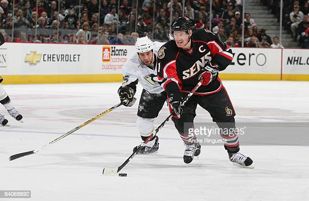 Daniel Alfredsson of the Ottawa Senators stickhandles the puck against Maxime Talbot of the Pittsburgh Penguins at Scotiabank Place on December 6,...