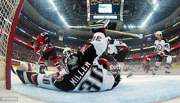 Daniel Alfredsson of the Ottawa Senators takes a shot as Ryan Miller of the Buffalo Sabres sprawls to make a save in game two of the Eastern...