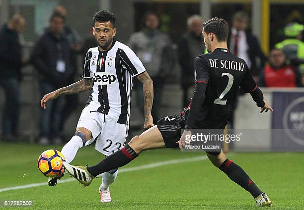 Daniel Alves da Silva of Juventus FC is challenged by Mattia De Sciglio of AC Milan during the Serie A match between AC Milan and Juventus FC at...