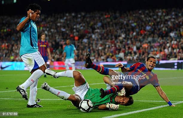 Daniel Alves of Barcelona falls over goalkeeper Diego Alves of Almeria as Wilmer Santiago of Almeria looks on during the La Liga match between...