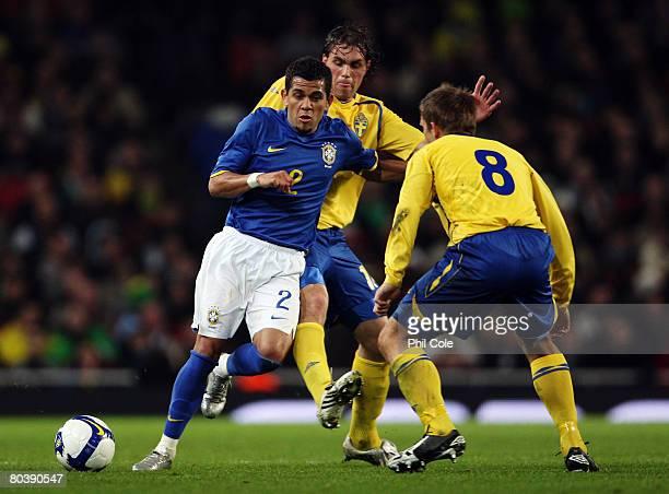 Daniel Alves of Brazil goes past Anders Svensson and Johan Elmander of Sweden during the International Friendly match between Sweden and Brazil at...