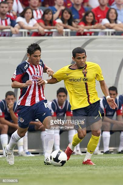 Daniel Alves of FC Balcelona moves for the ball against Edgar Solis of CD Guadalajara during a international friendly match on August 3, 2008 at...