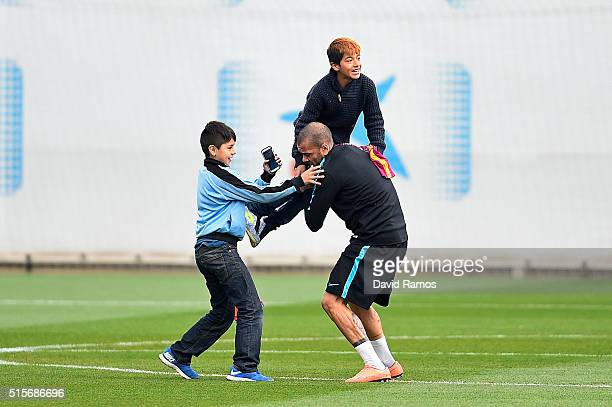 Daniel Alves of FC Barcelona greets young fans who ran onto the training pitch during a Barcelona training session ahead of the UEFA Champions League...