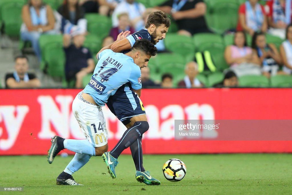 Daniel Arzani of Melbourne City tries to tackle Milos Ninkovic of Sydney FC during the round 20 A-League match between Melbourne City and Sydney FC at AAMI Park on February 10, 2018 in Melbourne, Australia.