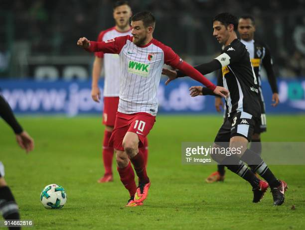 Daniel Baier of Augsburg and Lars Stindl of Moenchengladbach battle for the ball during the Bundesliga match between Borussia Moenchengladbach and FC...