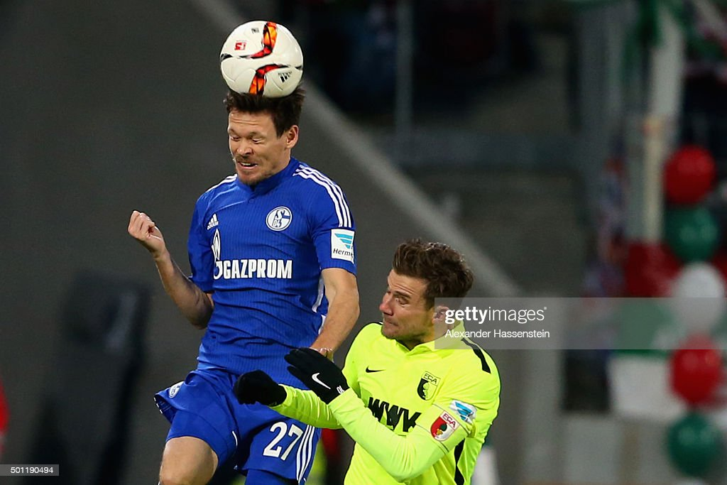 Daniel Baier (R) of Augsburg battles for the ball with Sascha Riether of Schalke during the Bundesliga match between FC Augsburg and FC Schalke 04 at WWK Arena on December 13, 2015 in Augsburg, Germany.