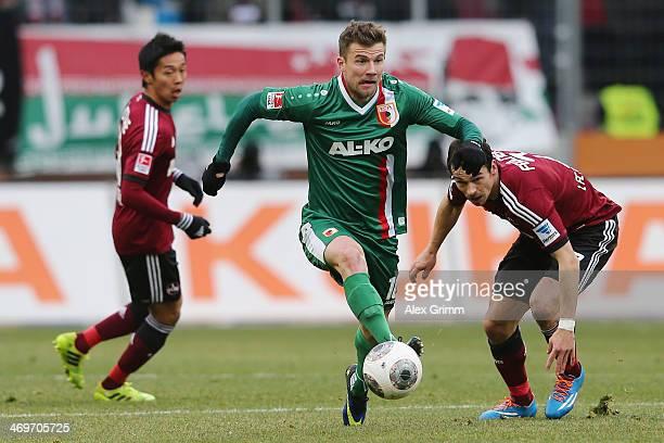 Daniel Baier of Augsburg eludes Markus Feulner and Hiroshi Kiyotake of Nuernberg during the Bundesliga match between FC Augsburg and 1 FC Nuernberg...