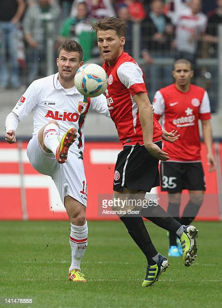 Daniel Baier of Augsburg fights for the ball with Eugen Polanski of Mainz during the German Bundesliga match between FC Augsburg and FSV Mainz 05 at...