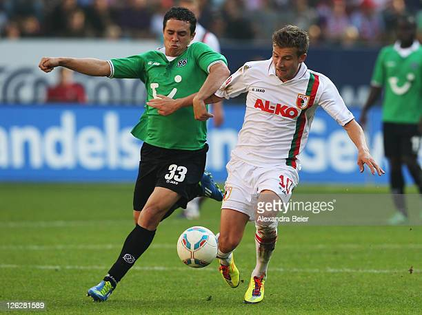 Daniel Baier of Augsburg fights for the ball with Manuel Schmiedebach of Hannover during the Bundesliga match between FC Augsburg and Hannover 96 at...
