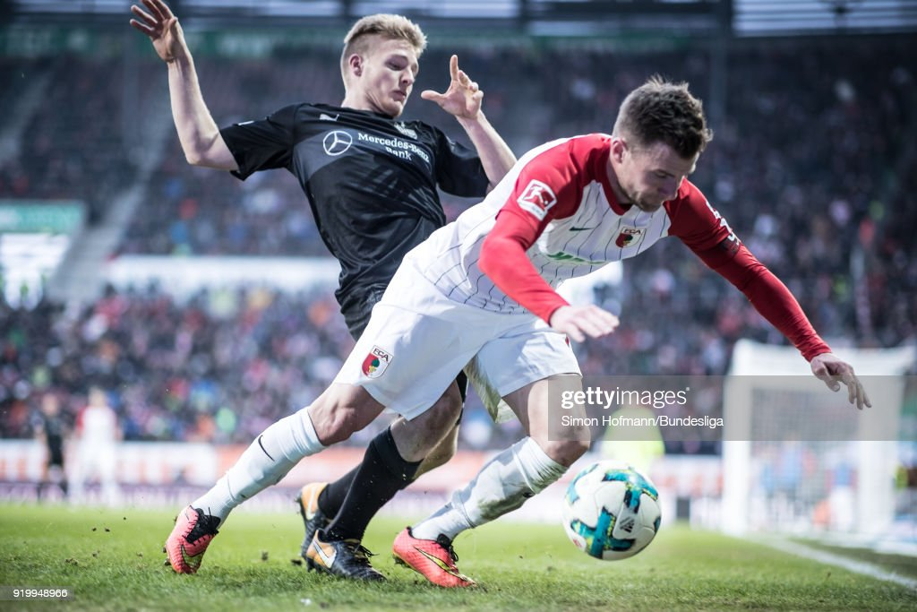 Daniel Baier of Augsburg is tackled by Santiago Ascacibar of Stuttgart during the Bundesliga match between FC Augsburg and VfB Stuttgart at WWK-Arena on February 18, 2018 in Augsburg, Germany.