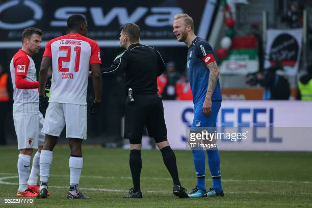 Daniel Baier of Augsburg speaks with Sergio Cordova of Augsburg referee Patrick Ittrich and Kevin Vogt of Hoffenheim during the Bundesliga match...