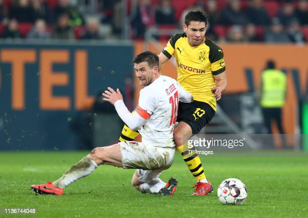 Daniel Baier of FC Augsburg and Raphael Guerreiro of Borussia Dortmund battle for the ball during the Bundesliga match between FC Augsburg and...