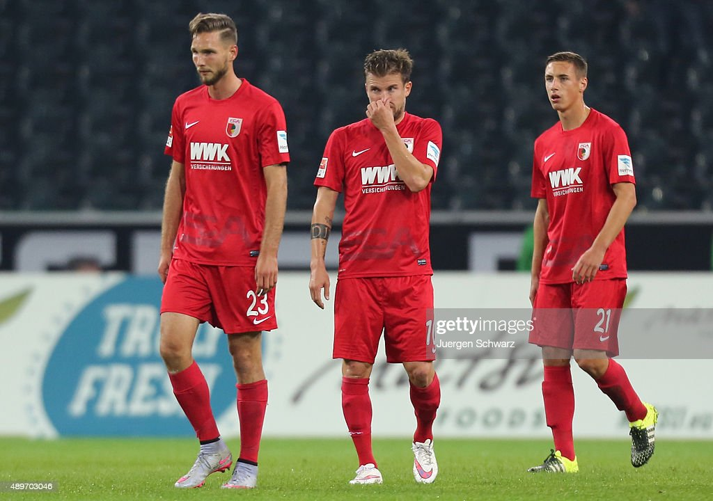 Daniel Baier (C) touches his nose between Tim Matavz (L) and Dominik Kohr during the Bundesliga match between Borussia Moenchengladbach and FC Augsburg at Borussia-Park on September 23, 2015 in Moenchengladbach, Germany.