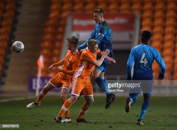 Daniel Ballard of Arsenal heads the ball away from Nathan Shaw and Owen Watkinson of Blackpool during the match between Blackpool and Arsenal at...