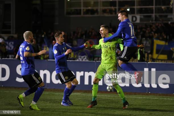 Daniel Batz of Saarbruecken celebrates with team mates after saving a penalty from Mathias Zanka Jørgensen of Fortuna Dusseldorf to give his side...