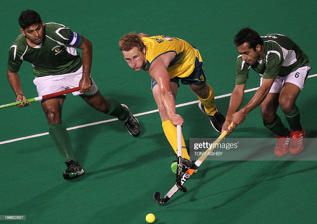 Daniel Beale of Australia (C) is pursued by Muhammad Imran and Rashid Mehmood of Pakistan (L) during their men's match at the International Super Series hockey tournament in Perth on November 22, 2012.
