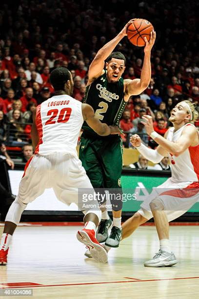 Daniel Bejarano of the Colorado State Rams tries to find an opening between Sam Logwood and Hugh Greenwood of the New Mexico Lobos during their game...