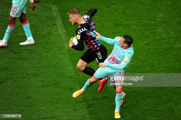 Daniel Bentley of Bristol City and Connor Roberts of Swansea City clash during the Sky Bet Championship match between Bristol City and Swansea City...