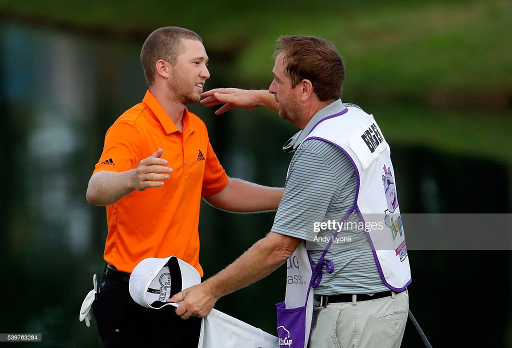 Daniel Berger celebrates with his caddie after winning the FedEx St. Jude Classic during the final round at TPC Southwind on June 12, 2016 in Memphis, Tennessee. Berger finished with a score of -13.