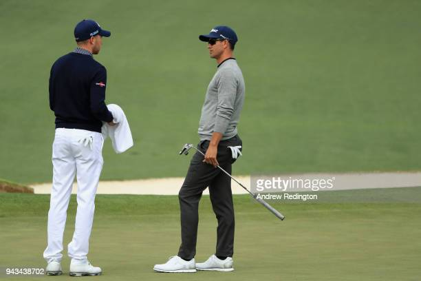 Daniel Berger of the United States and Adam Scott of Australia talk on the second green during the final round of the 2018 Masters Tournament at...