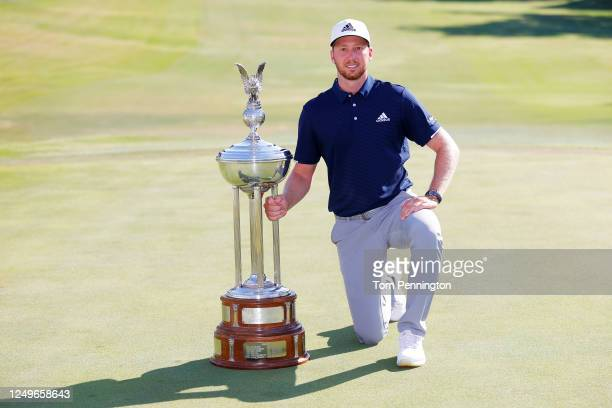 Daniel Berger of the United States celebrates with the Leonard Trophy after defeating Collin Morikawa of the United States in a playoff during the...