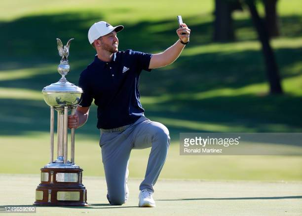 Daniel Berger of the United States takes a selfie as he celebrates with the Leonard Trophy after defeating Collin Morikawa of the United States in a...
