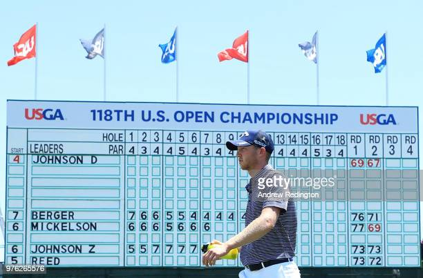 Daniel Berger of the United States walks in front of the leaderboard on the 14th green during the third round of the 2018 US Open at Shinnecock Hills...