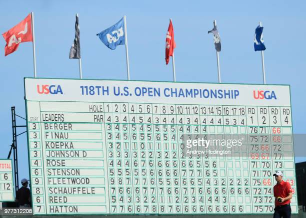 Daniel Berger of the United States walks past a leaderboard on the 14th hole during the final round of the 2018 US Open at Shinnecock Hills Golf Club...