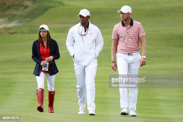 Daniel Berger of the US Team Captain's assistant Tiger Woods of the US Team and Erica Herman walk during Friday fourball matches of the Presidents...