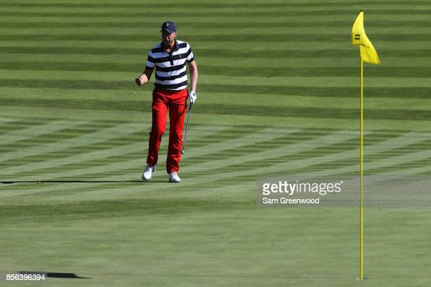 Daniel Berger of the US Team reacts to chipping in on the 11th green during Sunday singles matches of the Presidents Cup at Liberty National Golf...
