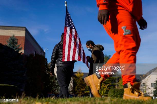 Daniel Billingslea of Detroit, holds and American flag while canvassing to get signatures to get a name on the ballot for Mayor outside the Greater...
