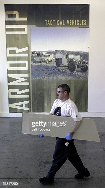 Daniel Blakey carries a ballistic panel part of ArmorWorks Ballistic Advantage Armor kit to the shipping area December 10 2004 in Tempe Arizona The...