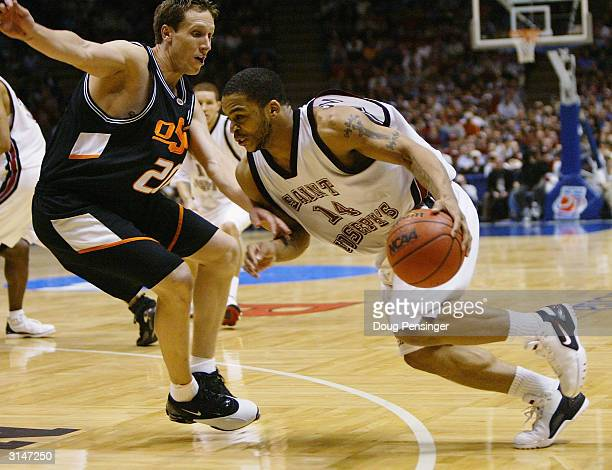 Daniel Bobik of the Oklahoma State Cowboys defends Jameer Nelson of the St Joseph's Hawks during their fourth round regional game of the NCAA...