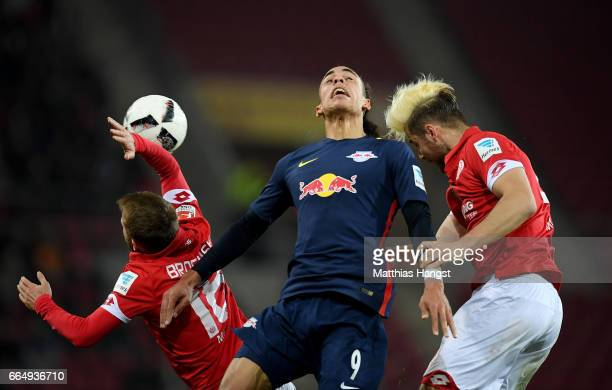 Daniel Borsinski and Alexander Hack of Mainz and Yussuf Poulsen of Leipzig head for the ball during the Bundesliga match between 1 FSV Mainz 05 and...